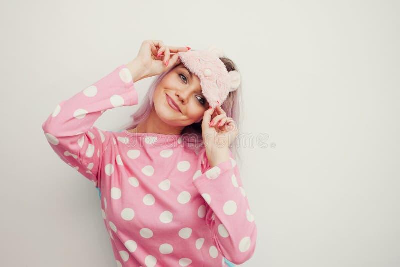 Buenos días Mujer joven sonriente Muchacha en pijamas y máscara rosados del sueño fotografía de archivo