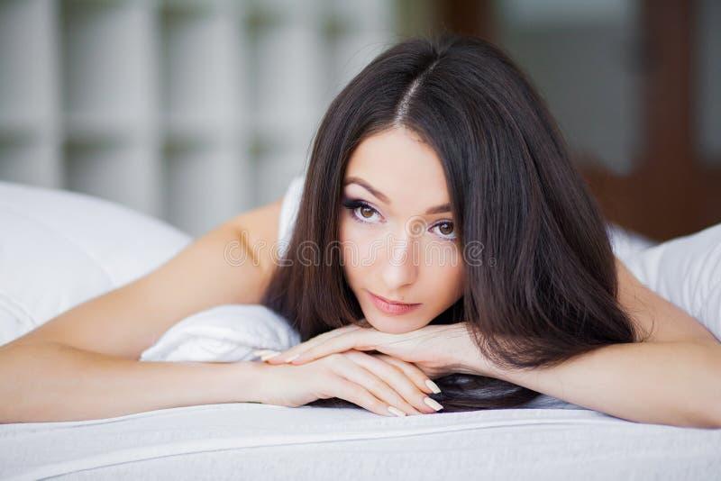 Buenos días Retrato de una sonrisa mujer morena bastante joven que se relaja en la cama blanca foto de archivo libre de regalías