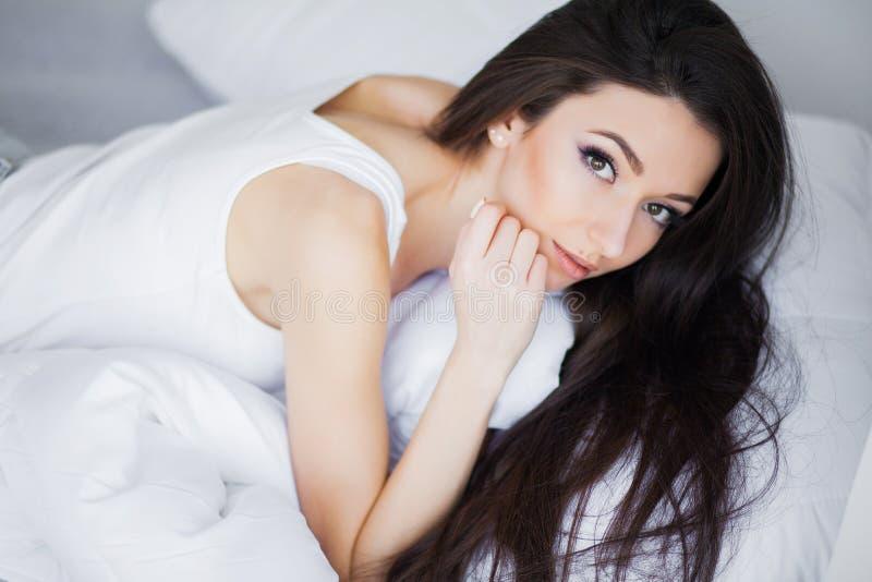 Buenos días Retrato de una sonrisa mujer morena bastante joven que se relaja en la cama blanca imágenes de archivo libres de regalías