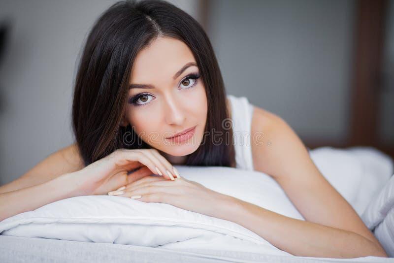 Buenos días Retrato de una sonrisa mujer morena bastante joven que se relaja en la cama blanca fotografía de archivo libre de regalías