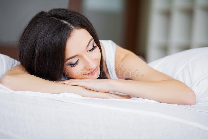 Buenos días Retrato de una sonrisa mujer morena bastante joven que se relaja en la cama blanca imagen de archivo