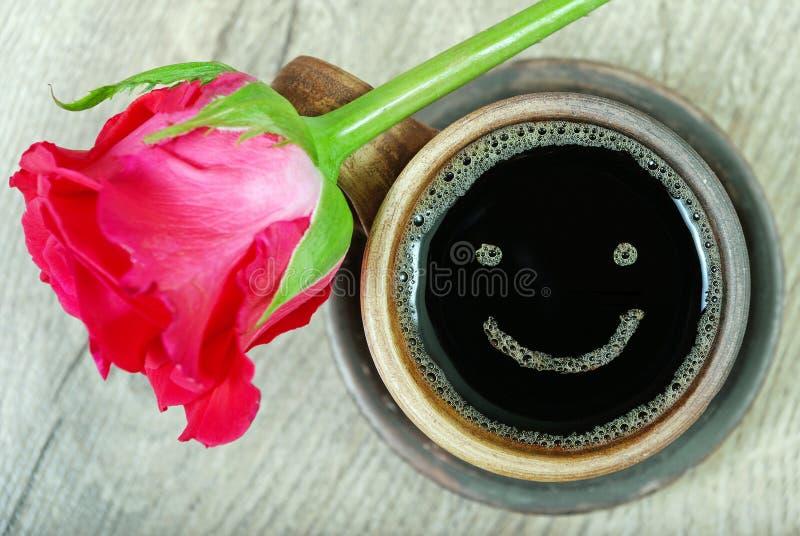 Buenos días una taza de café y de una rosa roja en una tabla de madera sonrisa de un día feliz foto de archivo libre de regalías