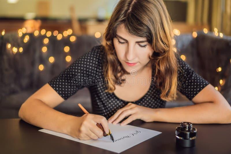 Buenos d?as El cal?grafo Young Woman escribe frase en el Libro Blanco Inscripci?n de letras adornadas ornamentales imagen de archivo libre de regalías