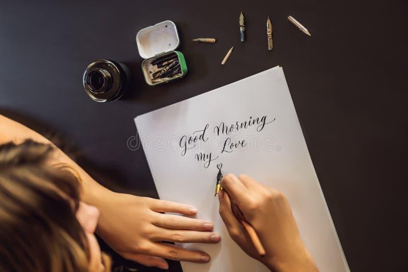 Buenos d?as El cal?grafo Young Woman escribe frase en el Libro Blanco Inscripci?n de letras adornadas ornamentales fotos de archivo