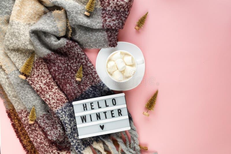 Bufanda caliente, acogedora del invierno y taza de café blanca con la melcocha blanca como marco en fondo rosado en colores paste imágenes de archivo libres de regalías