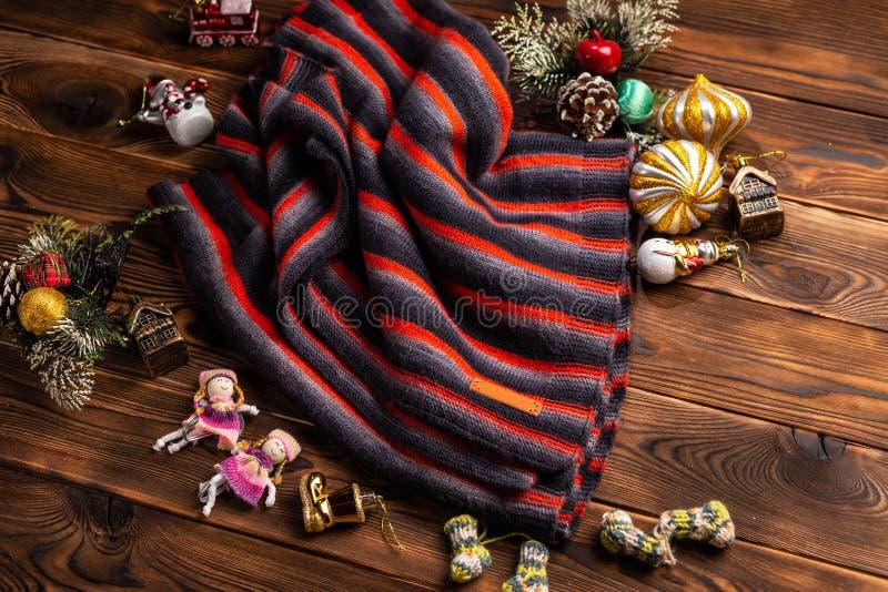Bufanda hecha punto en rayas y decoraciones negras, rojas y blancas de la Navidad en un fondo de madera foto de archivo