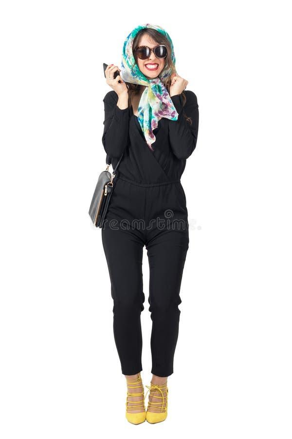 Bufanda que lleva y gafas de sol de la mujer hermosa enérgica con el teléfono móvil foto de archivo libre de regalías