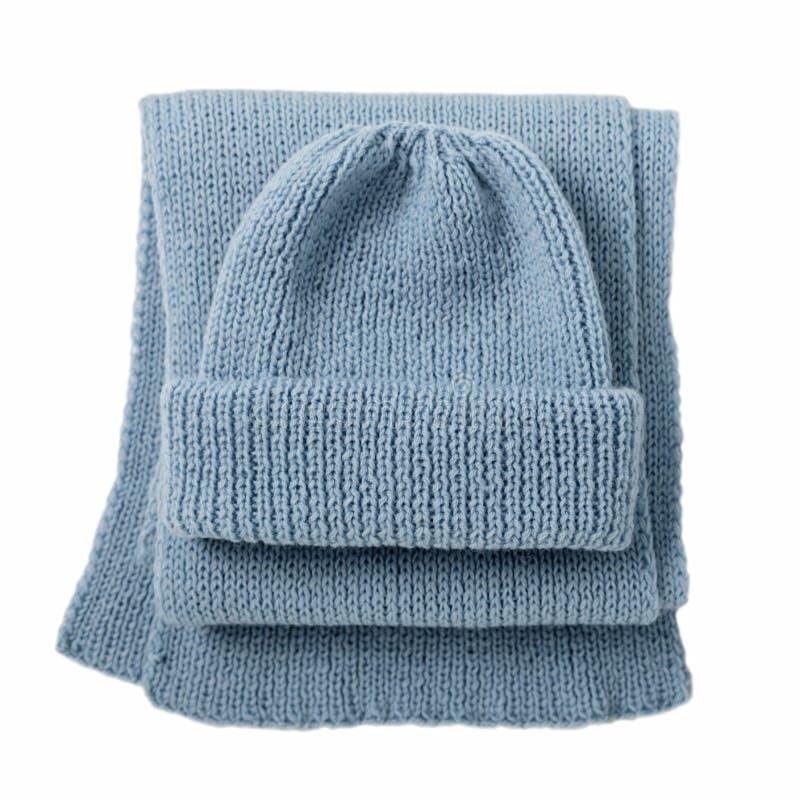 Bufanda y casquillo hechos punto del color azul en fondo blanco aislado foto de archivo libre de regalías