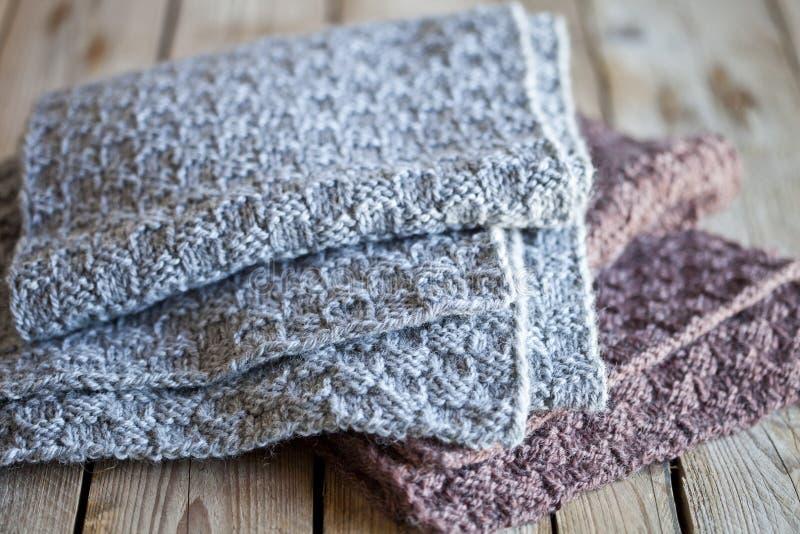 Bufandas grises y marrones de lana hechas punto imagenes de archivo