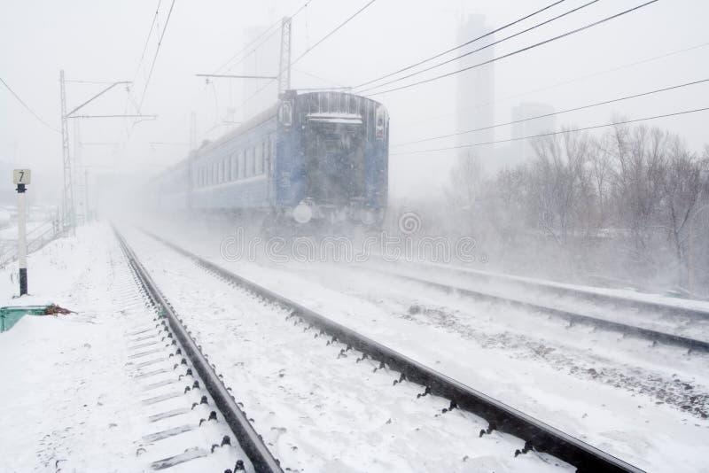 Bufera di neve e treno di passaggio fotografia stock libera da diritti