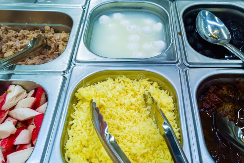 Bufete de ensaladas en envases en el queso rallado contrario, aceitunas, palillos del cangrejo, carne, huevos foto de archivo libre de regalías