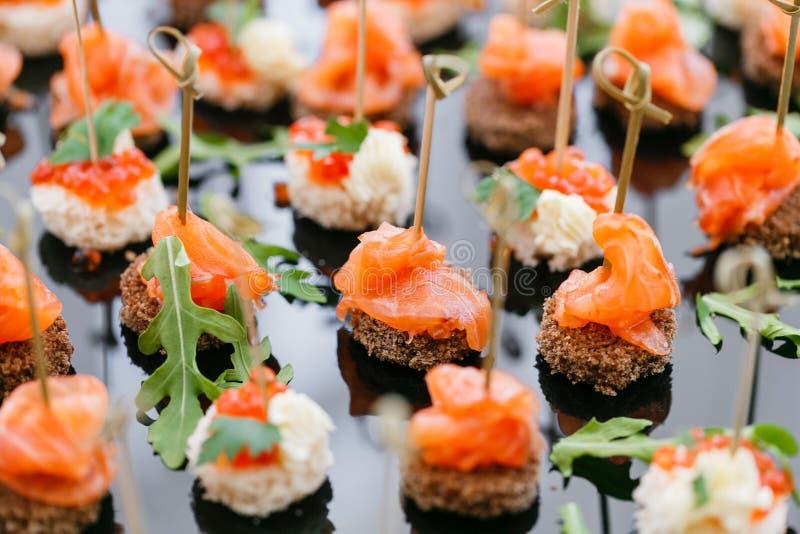Bufete no jantar de gala Variedade dos canapes Servi?o do banquete alimento da restaura??o, petiscos com salm?es e caviar centeio fotografia de stock