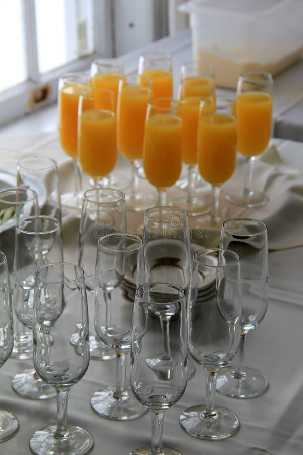 Buffétabellen med exponeringsglas fyllde med orange fruktsaft arkivbilder