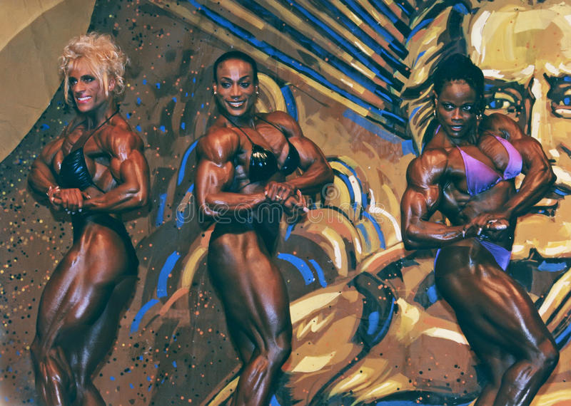 Buff Babes Posedown. Under the watchful eye of then IFBB head Joe Weider's mural, three top-flight pro women bodybuilders posedown at the IFBB Ms Olympia contest stock photo