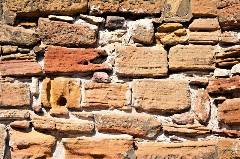 Rough hewn wall of weathered sandstone blocks. Buff, cream, ochre, red, orange, tan colored tones of natural sedimentary sandstone bricks piles and cemented stock image