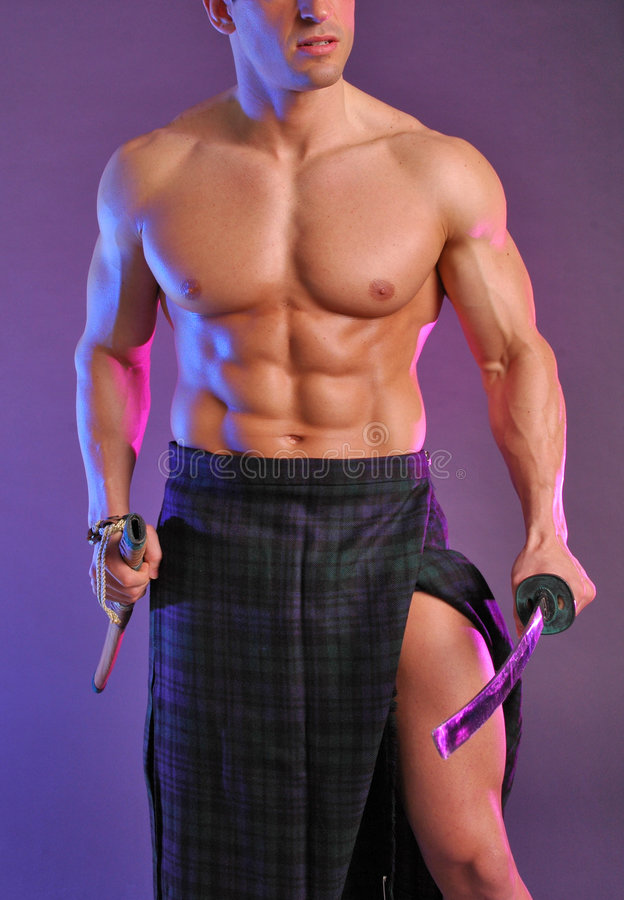 Buff scotsman. Well built male model in green and blue plaid kilt. he's holding two celtic swords