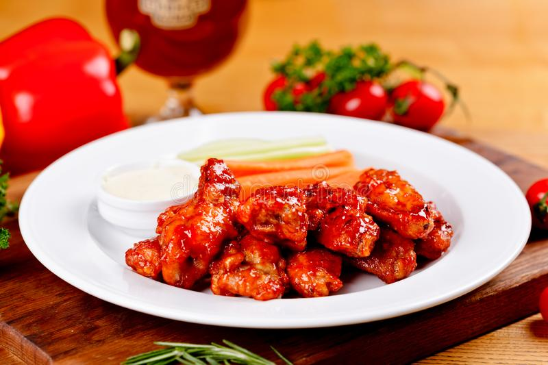 Buffalo chicken wings with blue cheese dip, carrots and celery sticks on white plate stock photography