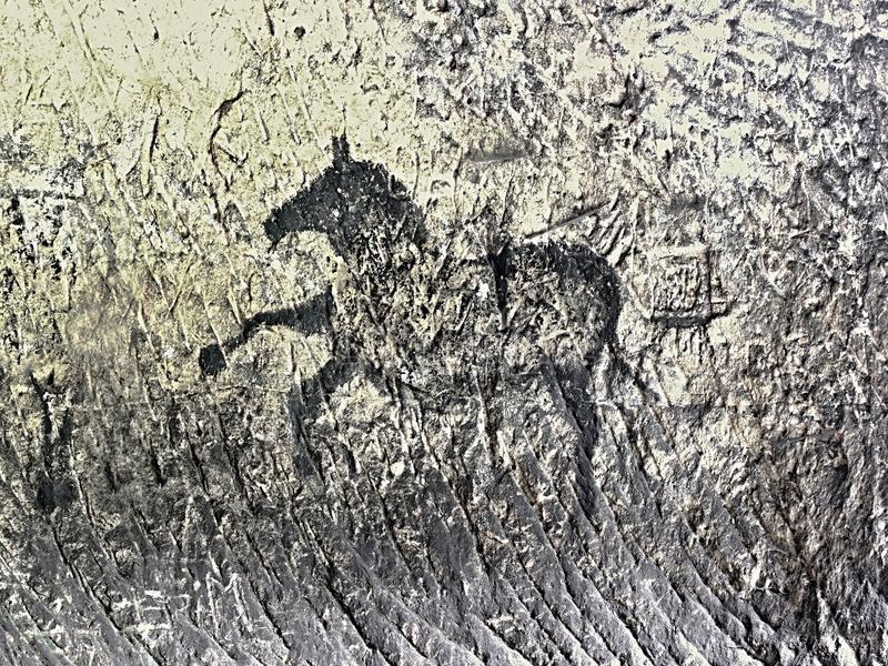 Buffalo hunting. Paint of human hunting on sandstone wall, prehistoric picture. Abstract children art in sandstone cave. Black carbon paint of horses on royalty free stock photos