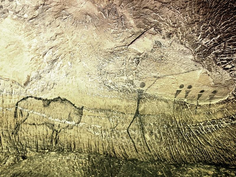 Buffalo hunting. Paint of human hunting on sandstone wall, prehistoric picture. Black carbon abstract children art in sandstone cave stock images