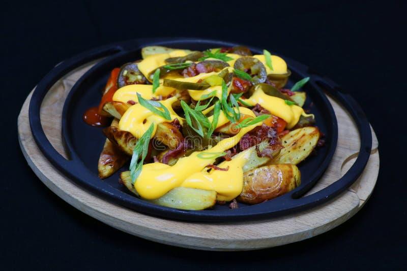 Buffalo potato wedges with cheese sauce and jalapeno stock photos