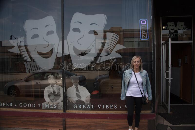Woman standing in front of a craft beer bar in Buffalo in the United States. BUFFALO, UNITED STATES - Jul 12, 2016: A woman standing in front of a craft beer bar royalty free stock image