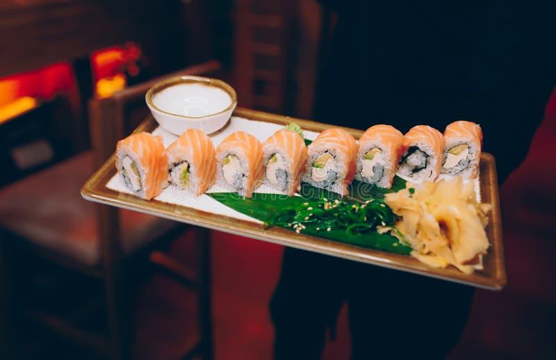 Buffet ahumado de la meseta de Philly del sushi en la noche que cena endecha plana resturant Alga marina y jengibre de color salm imágenes de archivo libres de regalías