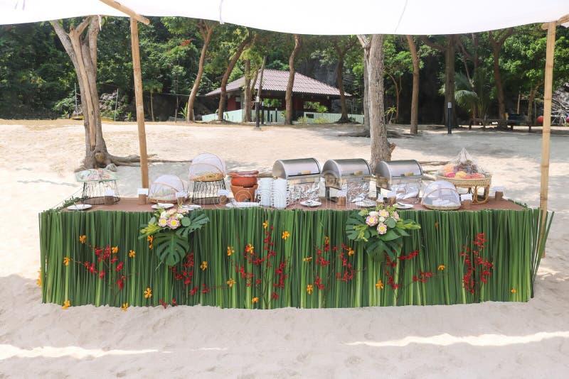 Buffet auf dem Strand, Linie Einrichtung für das Mittagessen an tropischem lizenzfreies stockbild