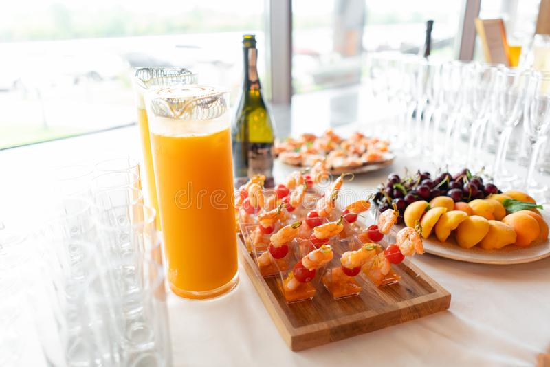 The buffet at the reception. Glasses of wine and champagne. Assortment of canapes on wooden board. Banquet service stock image