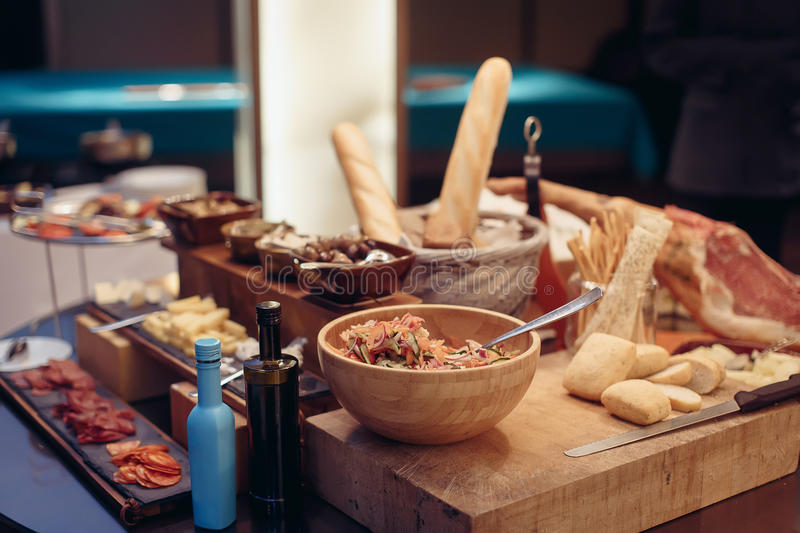 Buffet salad olive bread and jamon. Breakfast buffet with salad and olive bread jamon on a thick wooden board with a knife and souce. Soft focus stock photos
