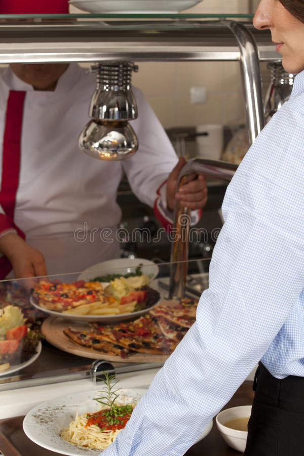 Buffet self-service. Food display women take meal royalty free stock images