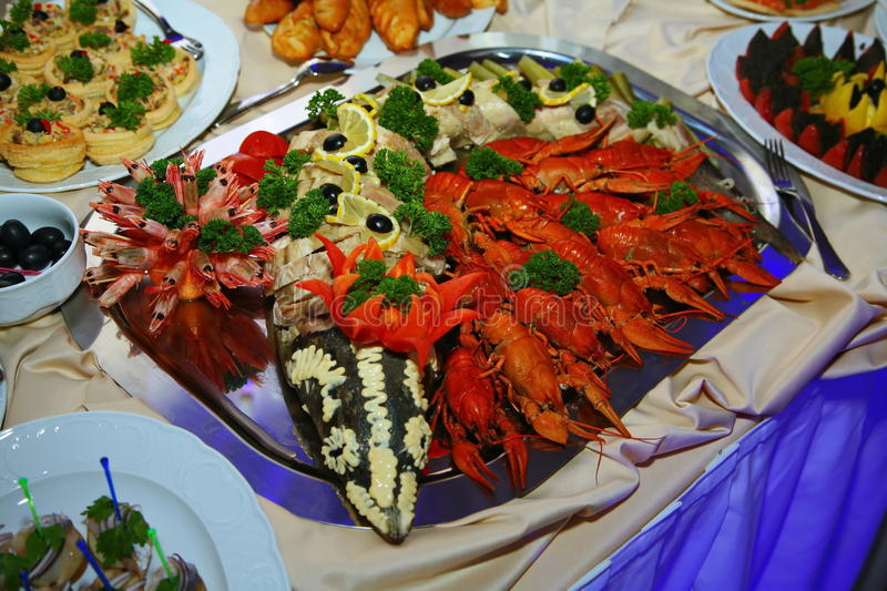 Buffet. snacks, finger food seafood: boiled red crayfish, shrimp and stuffed sturgeon on a large steel dish. About buffets for parties. Plate restaurant food stock image