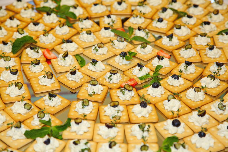 Buffet. snacks, finger food ( biscuits, crackers ) with soft curd cheese, olives and herbs on a large platter. About buffets for parties. Plate restaurant food royalty free stock images