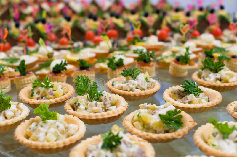 Buffet table. Many tartlets with meat salad under mayonnaise and parsley on buffet table, shallow DOF royalty free stock photo