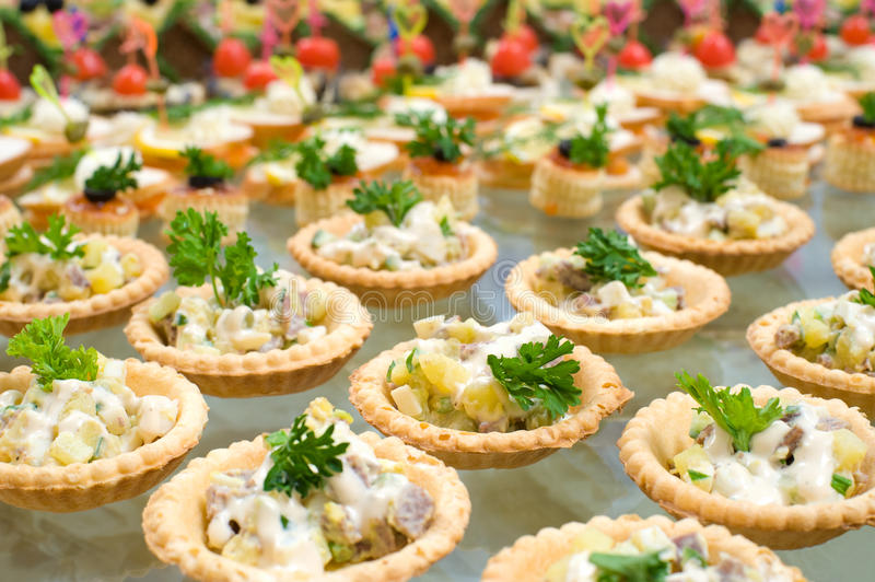 Buffet table. Many tartlets with meat salad under mayonnaise and parsley on buffet table, shallow DOF stock photo