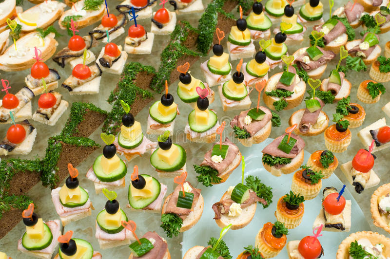 Buffet table. A lot of canapes with skewers and sandwiches on buffet table, shallow DOF stock photos