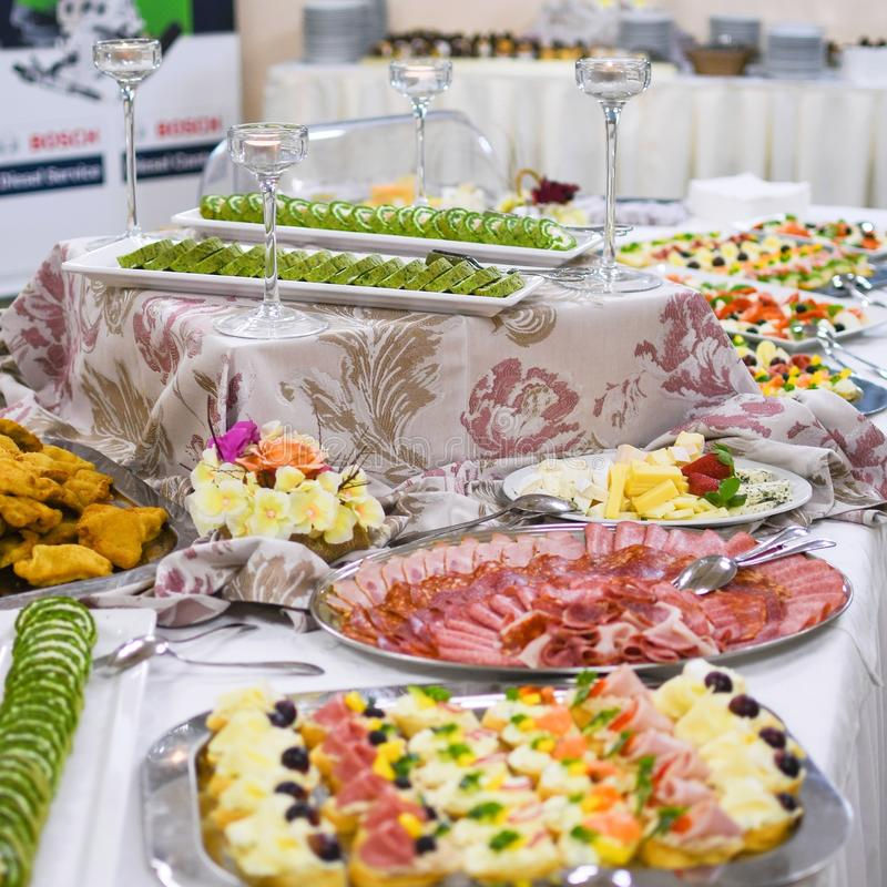 Buffet table full of food in small dishes, sweets and a fruit platter. royalty free stock images