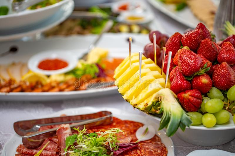 Buffet table of reception with cold snacks, salads and fruits. Buffet table of reception with cold snacks, meat, salads and fruits royalty free stock image