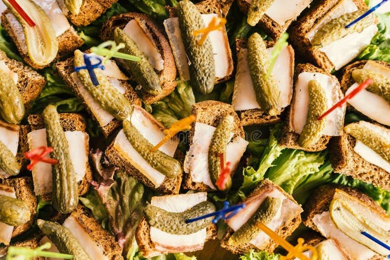 Buffetlijst met sandwiches van roggebrood, reuzel en ingelegde komkommers, hoogste meningsclose-up stock afbeelding