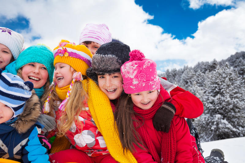 Bug lump of happy kids. Group of diversity looking happy kids hugging and playing together on winter sunny day royalty free stock image