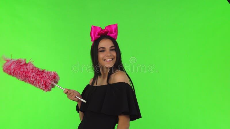 Bugar bärande rosa färger för ung härlig kvinna att posera med en dammtrasa royaltyfria bilder