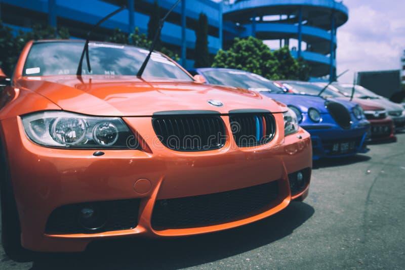 在蓝色Bugatti汽车旁边的橙色Bmw汽车 免版税库存图片