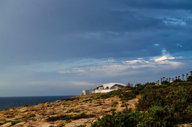 Buggiba, Malta 30 può 2019 - acquario nazionale di Malta il giorno piovoso con il cielo e le nuvole scuri drammatici fotografia stock libera da diritti