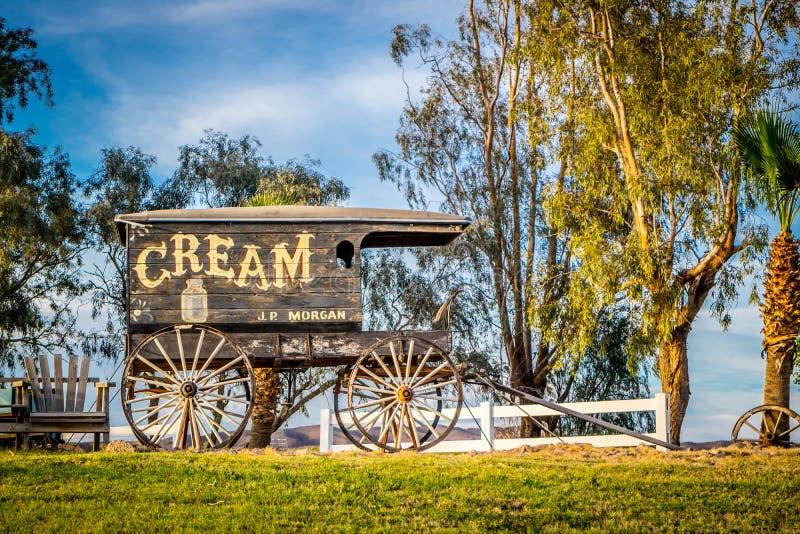 A buggy cart with light brownish low-wheeled carriage in Yuma, Arizona. Yuma, AZ, USA - April 7, 2017: A vintage JP Morgan ice cream horse drawn carriage royalty free stock image