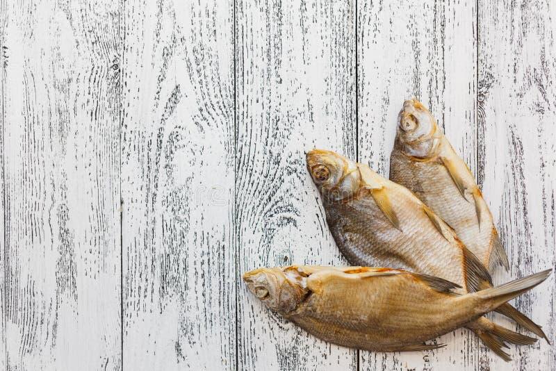 Bugia dell'orata di tre pesci essiccati su una tavola di legno leggera immagini stock