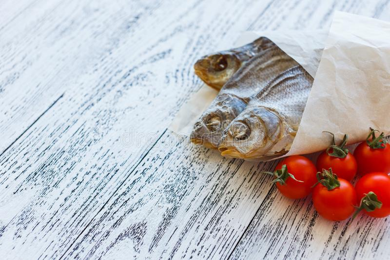 Bugia dell'orata di tre pesci essiccati su una tavola di legno leggera fotografia stock libera da diritti