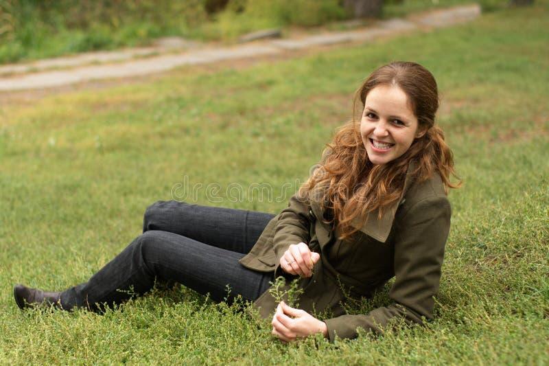 Bugia della donna di Redhead sull'erba fotografia stock libera da diritti