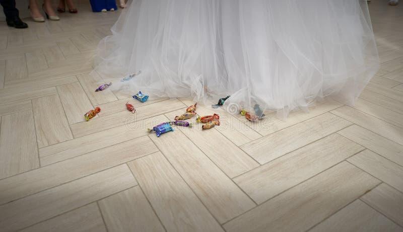 Bugia delle caramelle sul pavimento accanto alla fine della sposa fotografie stock