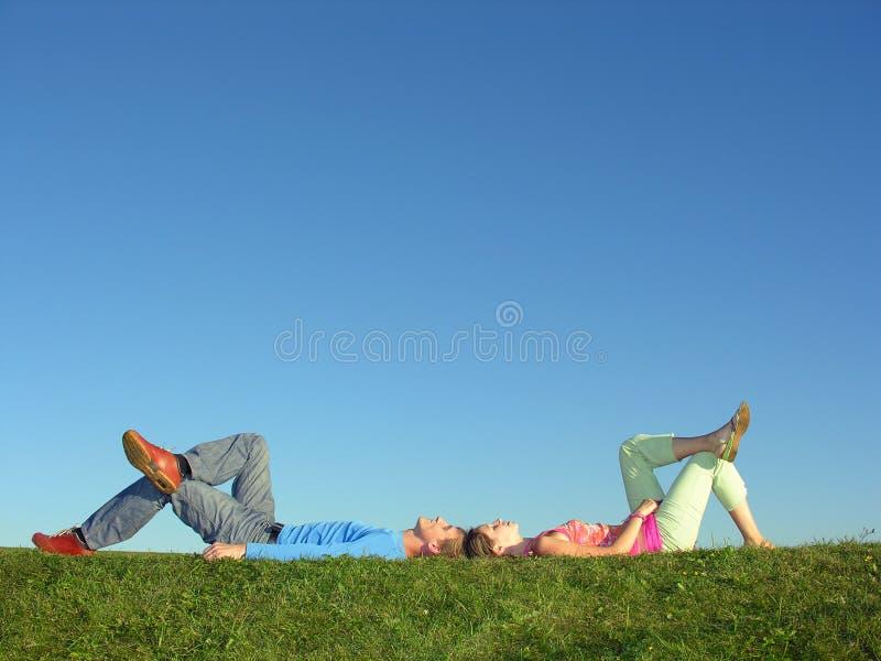 Bugia delle coppie su cielo blu fotografia stock