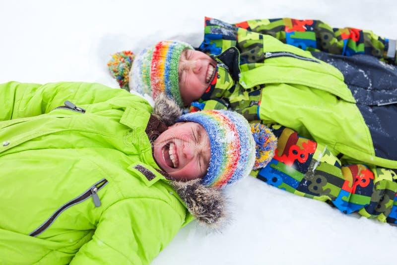 Bugia felice allegra dei ragazzi su neve, immagini stock