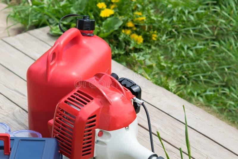 Bugia rossa della scatola metallica della falciatrice da giardino e del combustibile su una tavola di legno contro un prato ingle fotografia stock libera da diritti